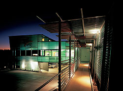 Looking along the entry ramp towards the entry verandah on the south elevation. The building is organized as two intersecting boxes, with undercroft carpark and service space. Image: Scott Burrows