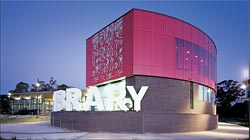 "The playful Elyard Street frontage of the Narellan Library, which provides access to the community and youth services wing of the building. The three-dimensional ""library"" supergraphic encloses an outdoor area for a cafe. Image: Tyrone Brannigan"