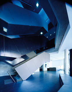 The dramatic scissor stair rises up the slim atrium space from the foyer. The intertwining black-and-white stairs lead to different destinations.